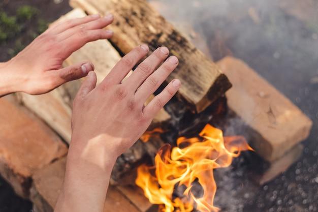 Mãos humanas perto da chama quente laranja. preparação de churrasco de primavera. muita fumaça. tijolos e lenha laranja. hora de descanso