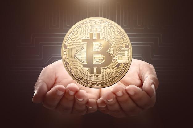 Mãos humanas segurando bitcoin dourado