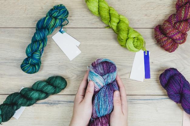 Mãos humanas segurando bola de lã e suprimentos de tricô na mesa de madeira