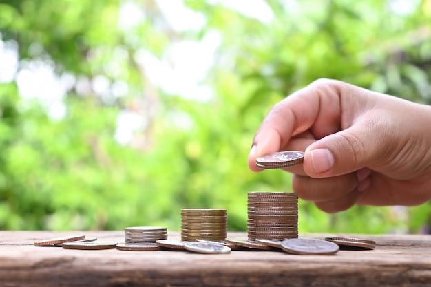 Mãos humanas segurando moedas e pilhas de moedas em ideias financeiras e de investimento de piso de madeira.