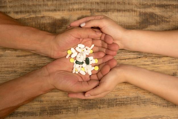 Mãos humanas segurando um monte de comprimidos isolados em um fundo de madeira com copyspace. conceito de saúde e medicina, tratamento, medicação, apoiando as mãos, recuperando-se.