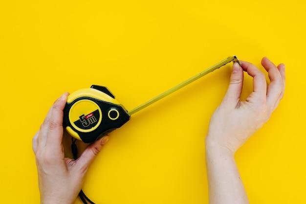 Mãos humanas segurando uma fita métrica em fundo amarelo.