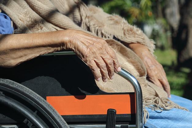 Mãos idosas em uma cadeira de rodas.
