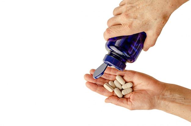 Mãos idosas femininas segurando comprimidos ou vitaminas. isolado no branco