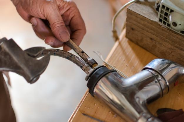 Mãos idosas que fixam a torneira de água com chave inglesa, fim acima.
