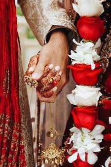 Mãos indianas autênticas dos noivos que mantêm-se junto no vestuário tradicional do casamento