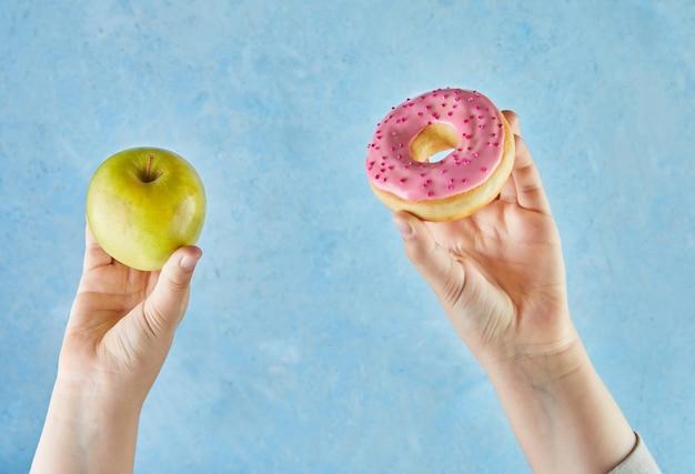 Mãos infantis com uma maçã e donut sobre fundo azul.