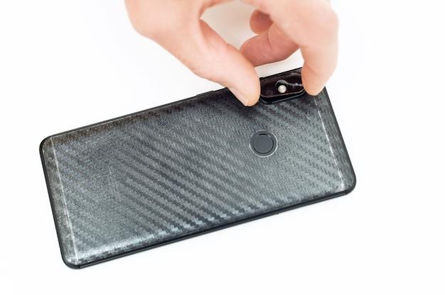 Mãos instalando um vidro protetor na lente traseira do smartphone.