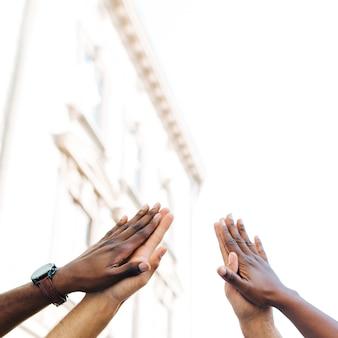 Mãos interculturais de baixo ângulo unidas