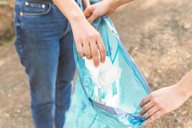 Mãos, jogar, lixo, em, sacola plástica