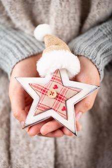 Mãos jovens de conceito de inverno segurando uma decoração de natal. idéia de decoração de natal. decoração de natal nas mãos de uma mulher, fundo com bokeh ouro.