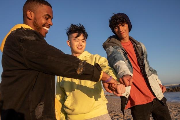 Mãos juntas, melhores amigos, meninos adolescentes na praia