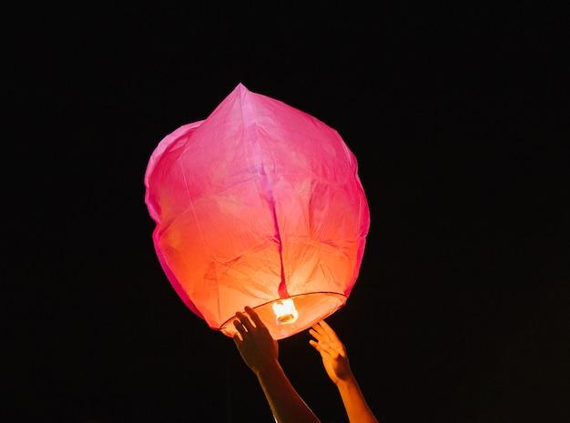 Mãos lançam uma lanterna de papel para o céu noturno. dentro da lanterna, o fogo queima em vermelho. uma bela tradição.