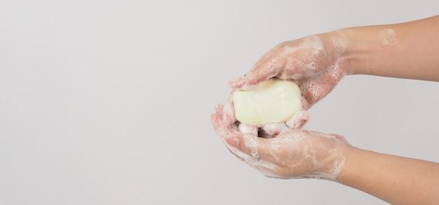 Mãos, lavagem gesto com sabão em barra e bolhas em fundo branco.