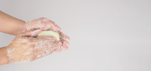 Mãos, lavagem gesto com sabão em barra e bolhas em fundo branco. Foto Premium