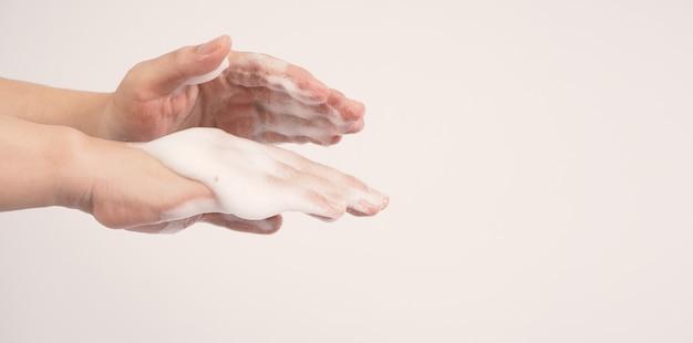 Mãos, lavagem gesto com sabonete de espuma em fundo branco.