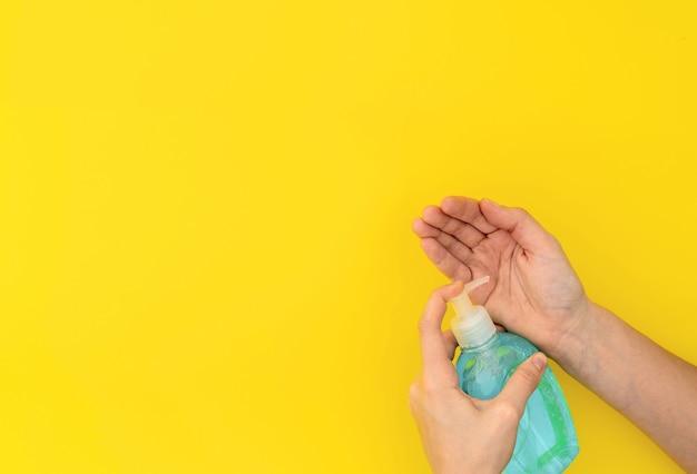 Mãos lavando com sabonete líquido azul ou desinfetante. vista superior em fundo amarelo