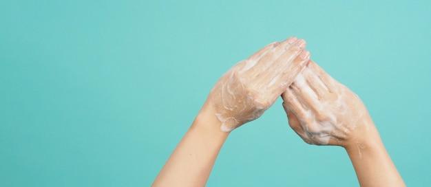 Mãos lavando gesto com sabonete de espuma em fundo de hortelã ou azul tiffany.