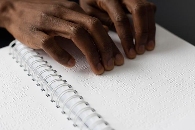 Mãos lendo braille de perto