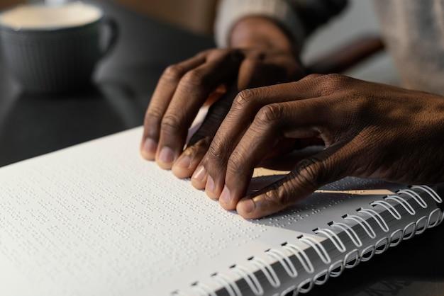 Mãos lendo caderno braille