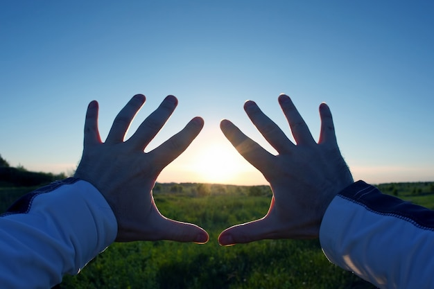 Mãos levantadas sobre o pôr do sol
