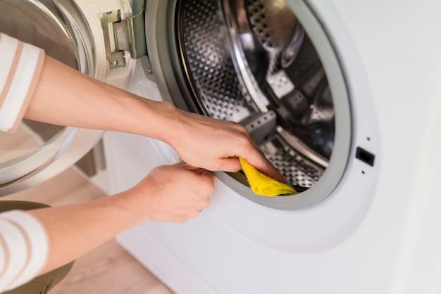 Mãos limpando dentro da máquina de lavar roupa