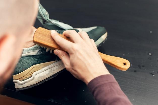Mãos limpando tênis de camurça