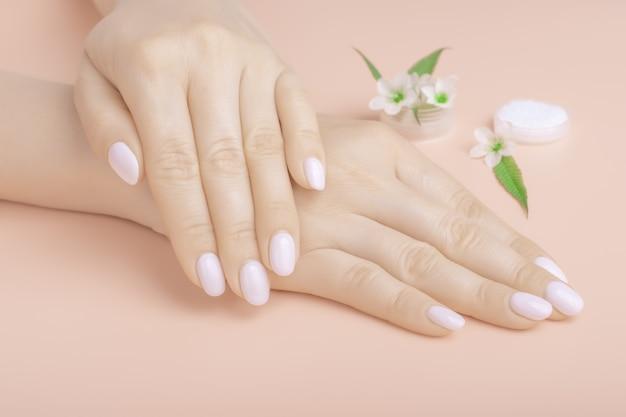 Mãos lindas com flores silvestres em cima da mesa, cosméticos anti-envelhecimento e anti-rugas para as mãos. cuidados com a pele e beleza, hidratação da pele e spa