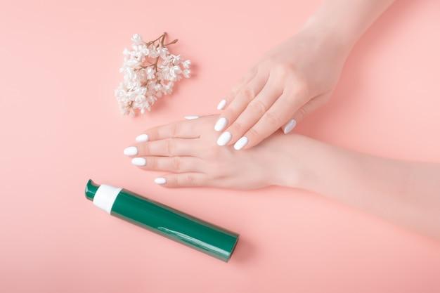 Mãos lindas com manicure perfeita e flor branca, aplicar loção para as mãos, conceito de cosméticos naturais de cuidados com a pele
