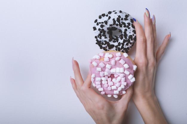 Mãos lindas femininas com manicure elegante segurando rosquinhas