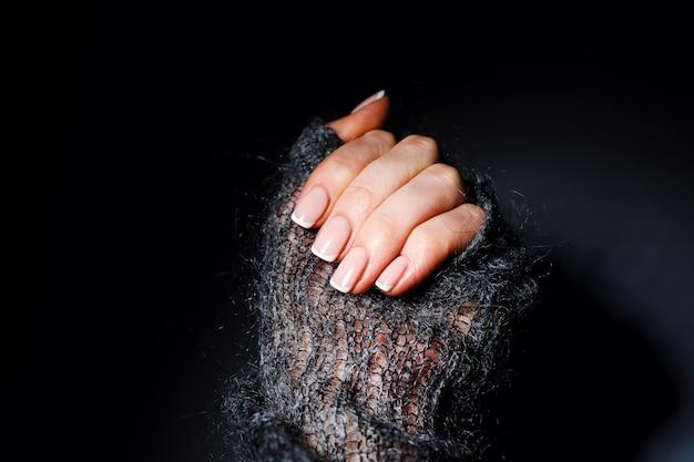 Mãos macias femininas com bela manicure francesa