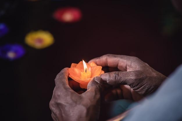 Mãos mais velhas segurando a luz de velas e orando por uma boa vida e paz das pessoas