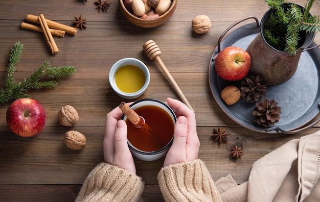 Mãos mantêm a caneca de aroma chá de maçã de natal com canela em uma mesa de madeira. vista do topo