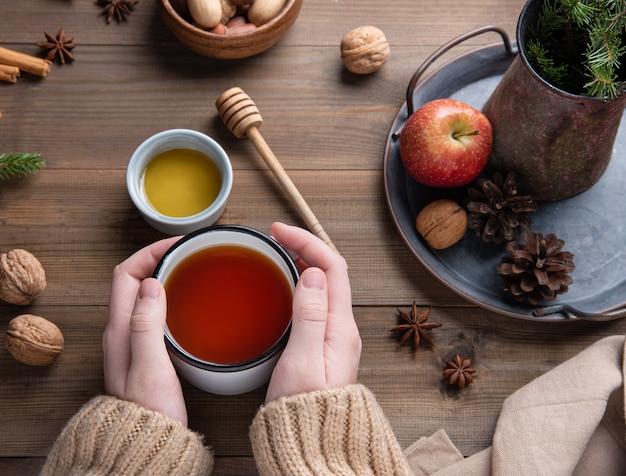 Mãos mantenham a xícara de chá de maçã aroma de natal com canela em uma mesa de madeira. vista do topo