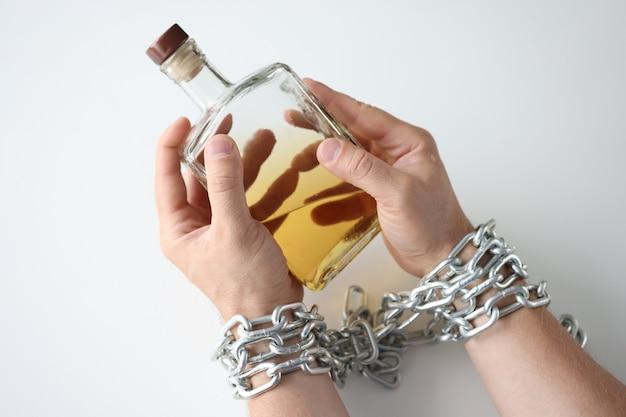 Mãos masculinas amarradas com corrente e segurando uma garrafa do conceito de dependência de álcool e alcoolismo
