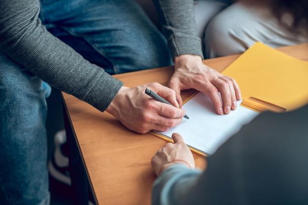 Mãos masculinas assinando documento e mão do corretor