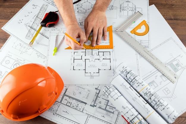 Mãos masculinas, capacete alaranjado, lápis, desenhos de construção arquitectónicos, fita métrica.