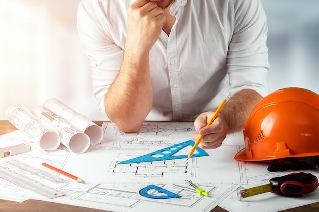 Mãos masculinas, capacete laranja, lápis, desenhos arquitetônicos, fita métrica