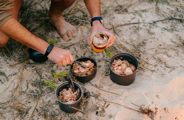 Mãos masculinas colocando comida em vasos na areia.