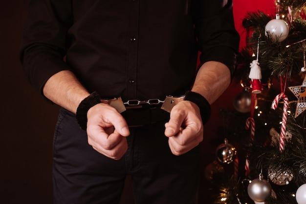 Mãos masculinas com algemas bdsm para submissão e dominação no contexto de uma árvore de natal no feriado de ano novo