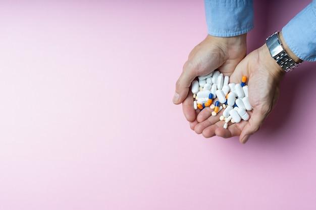 Mãos masculinas com camisa azul e relógio de pulso prateado segurando um punhado de medicamentos em comprimidos e cápsulas em formatos e cores variadas