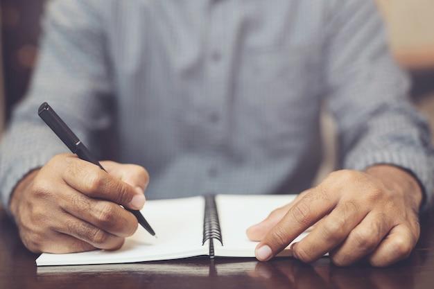 Mãos masculinas com caneta escrevendo no caderno
