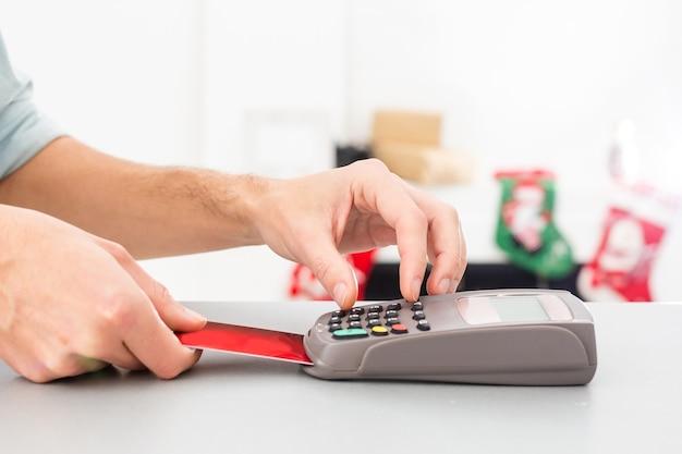 Mãos masculinas com cartão de crédito na máquina de cartão ou terminal pos isolado no fundo branco