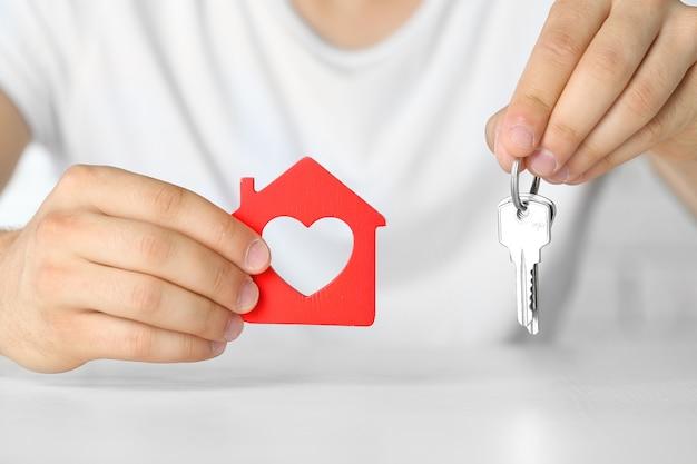 Mãos masculinas com casa e chaves, closeup
