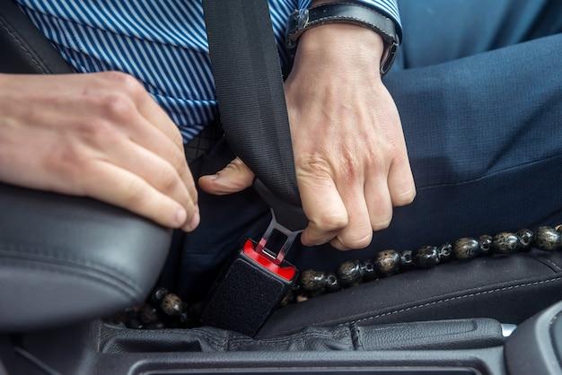 Mãos masculinas com cinto de segurança no carro.