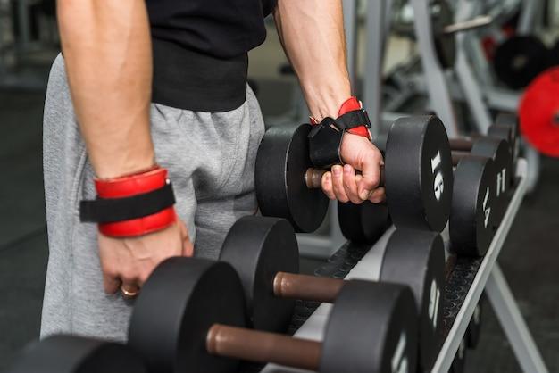 Mãos masculinas com halteres na academia fecham