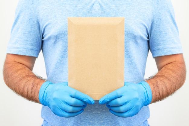 Mãos masculinas com luvas médicas seguram um envelope com documentos. serviço de entrega. correios.