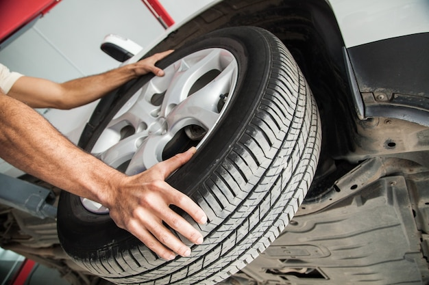 Mãos masculinas com pneus de automóvel no fundo