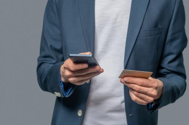 Mãos masculinas com smartphone e cartão de crédito