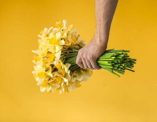 Mãos masculinas com um buquê de narcisos amarelos.